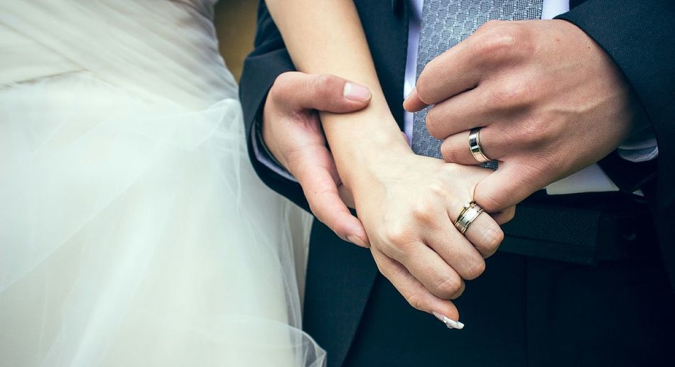Close-up of married couple holding hands