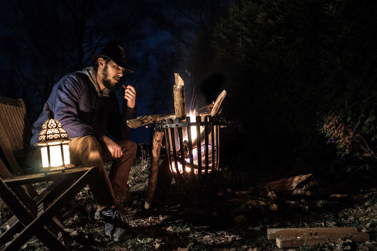 Man Sitting By Fire Pit At Night