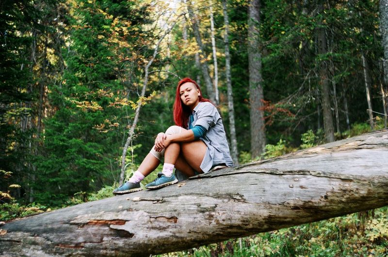 Portrait of young woman sitting on tree trunk in forest