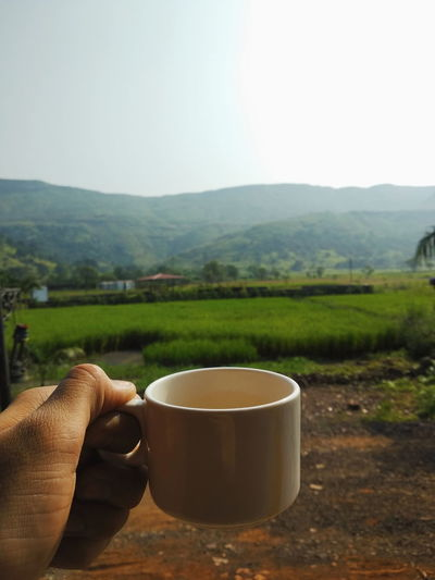 Coffee cup on table by mountains against sky