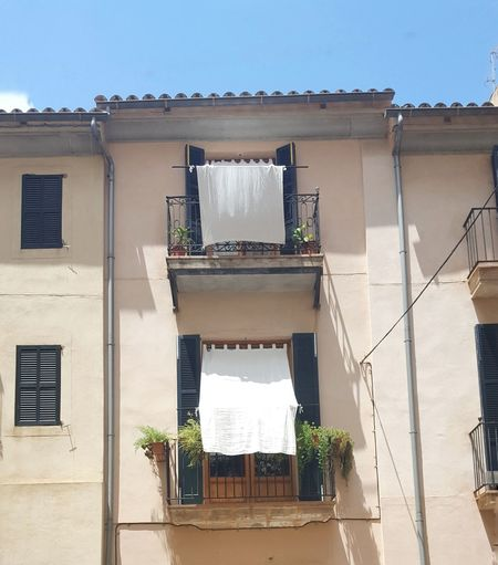 In need of shadow Windows Feel The Journey Original Experiences Facades Pastel Colors Wall Architectural Detail Outdoors Cropped Houses Old Architecture Hot Summer Day Sunshine Shadow Curtains Drape White Linen Feel The Heat Traveling Streets Of Mallorca Siesta Nap Looking Up No People Showcase June