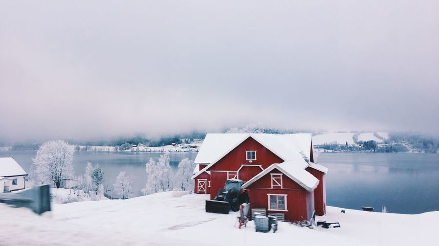 House on snow covered land against sky