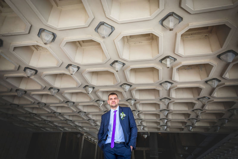 Low Angle Portrait Of Handsome Bridegroom Standing Against Patterned Ceiling