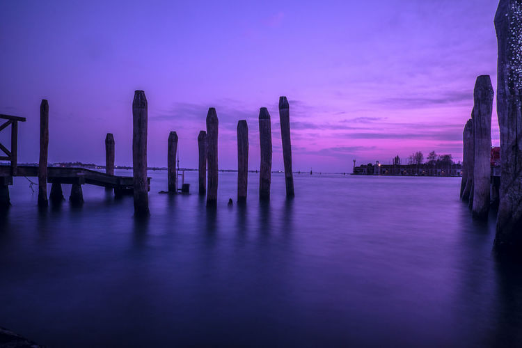 Wooden posts in sea against sky at sunset