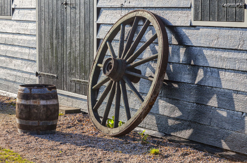 Old wooden wheel and a barrel naer the barn wall. Barn Objects Obsolete Old-fashioned Transportation Wall Barrel No People Old-fashioned Outdoors Vintage Wagon Wheel Wheel Wood - Material Wooden Wooden Things