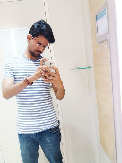 Young Man Taking Selfie With Mobile Phone At Home