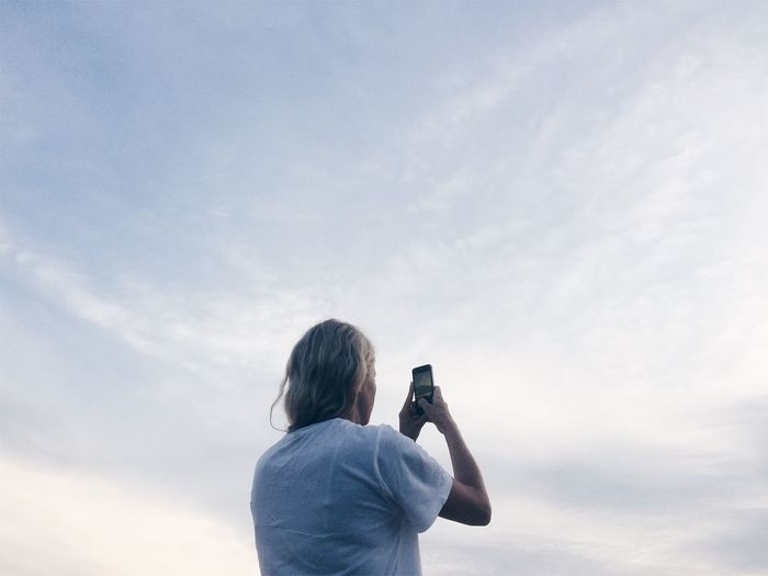 Low Angle View Of Woman Photographing Sky