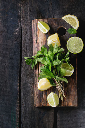 Sliced Lime and lemons with bunch of fresh mint on wooden cutting board over old wood background. Top view Food And Drink Food Freshness Healthy Eating Directly Above Herb Lemon Leaf SLICE Fruit Plant Part Mint Leaf - Culinary Citrus Fruit Lime Lemonade Ingredients Dark Chopping Board