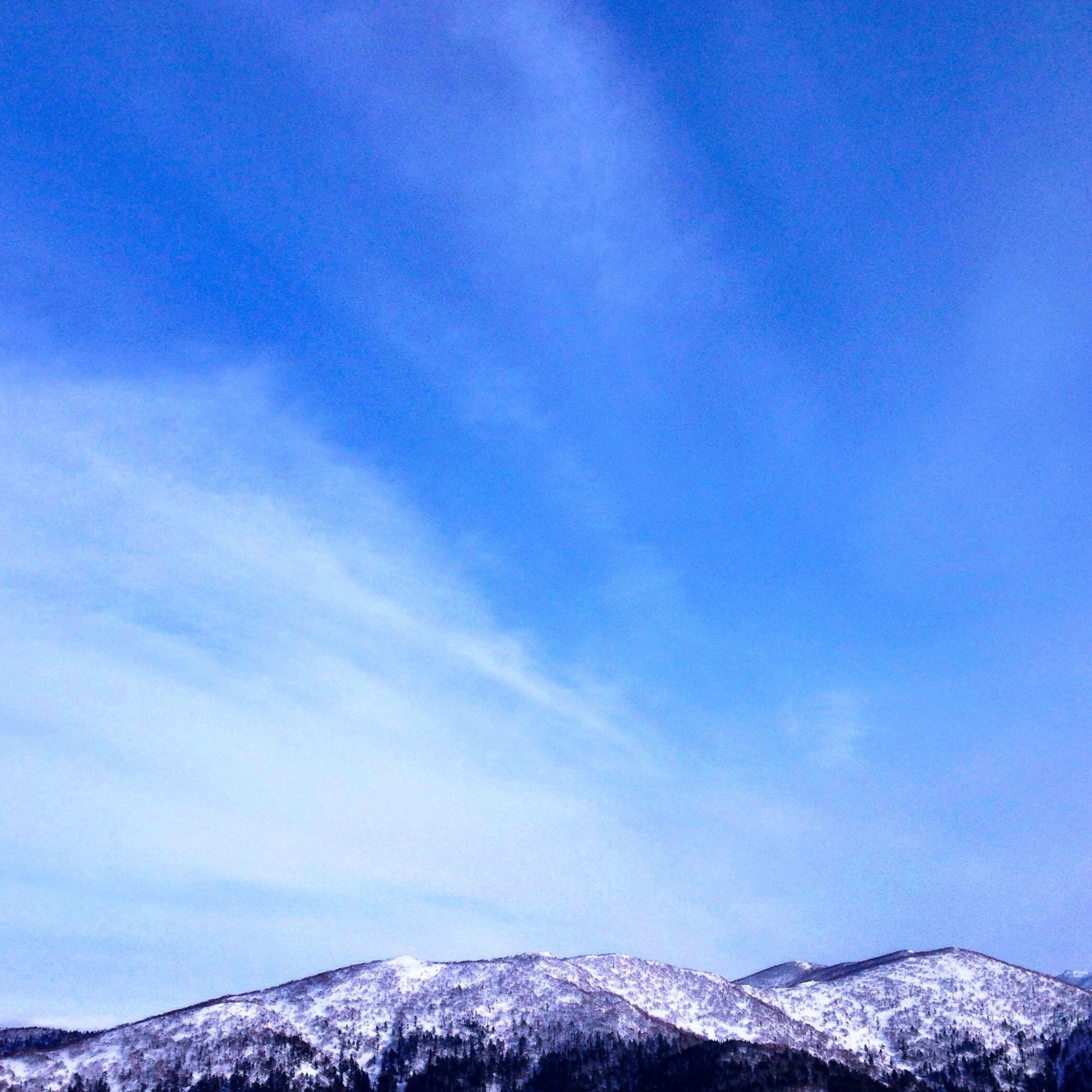 snow, sky, winter, blue, nature, cold temperature, mountain, beauty in nature, tranquility, low angle view, scenics, outdoors, cloud - sky, day, no people, tree