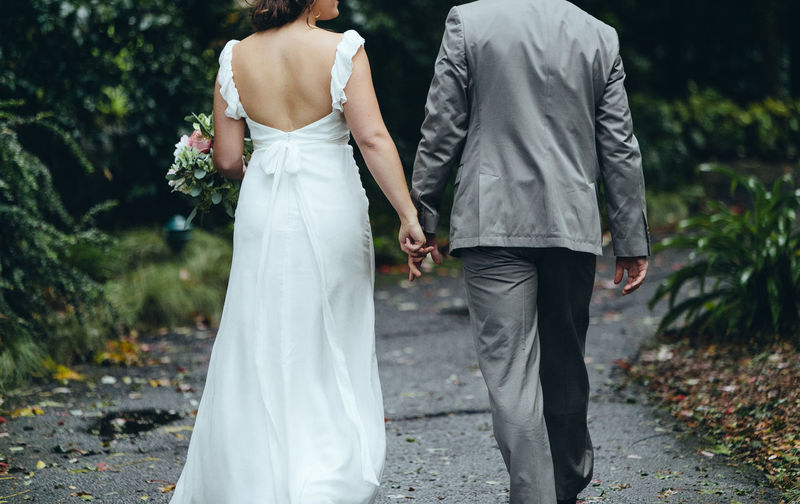 Rear view of newlywed couple holding hands while walking on footpath