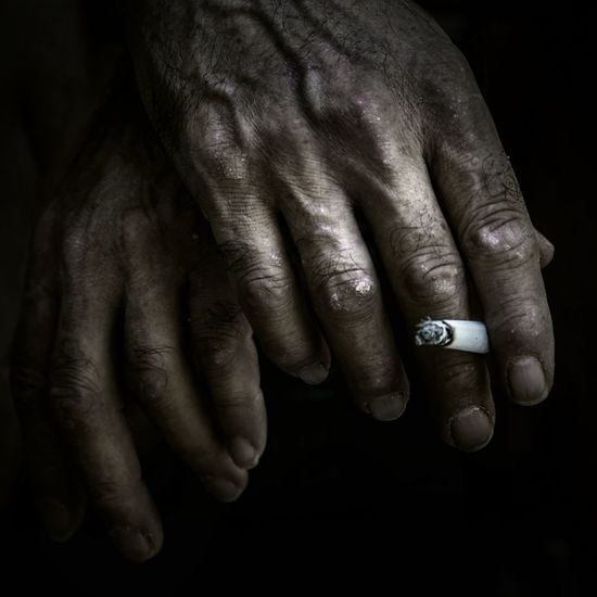 Cropped Hand Holding Cigarette Against Black Background