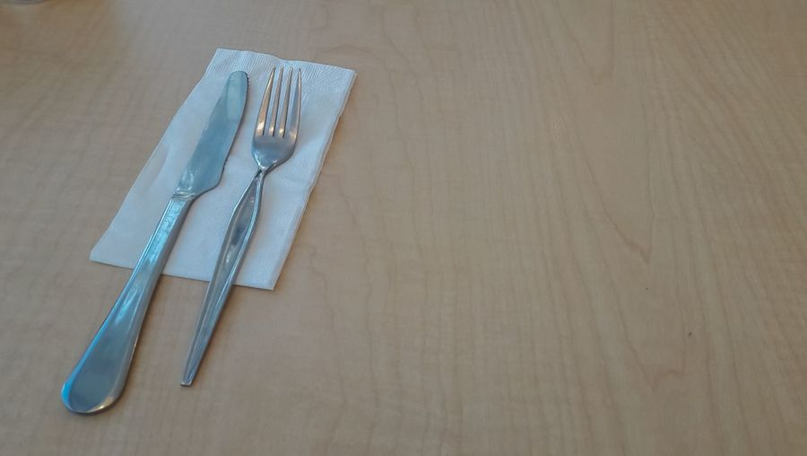 Close-up of eating utensils and tissue paper on table