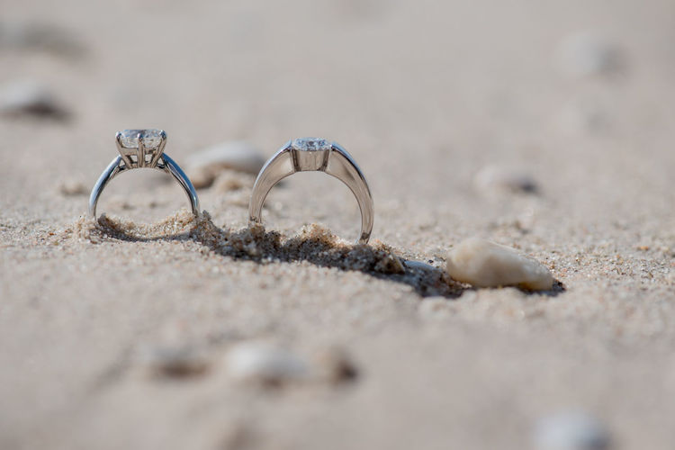 Two wedding rings on sand texture with by the sea. By The Sea Love Relationship Weddings By The Sea Beach Close-up Rings Couple - Relationship Cricle Diamond Ring Engagement Ring Jewelry Nopeople Outdoors Platinum Ring Sand Sand Texture Sea Sea Side Shell Silver Colored Wedding Rings