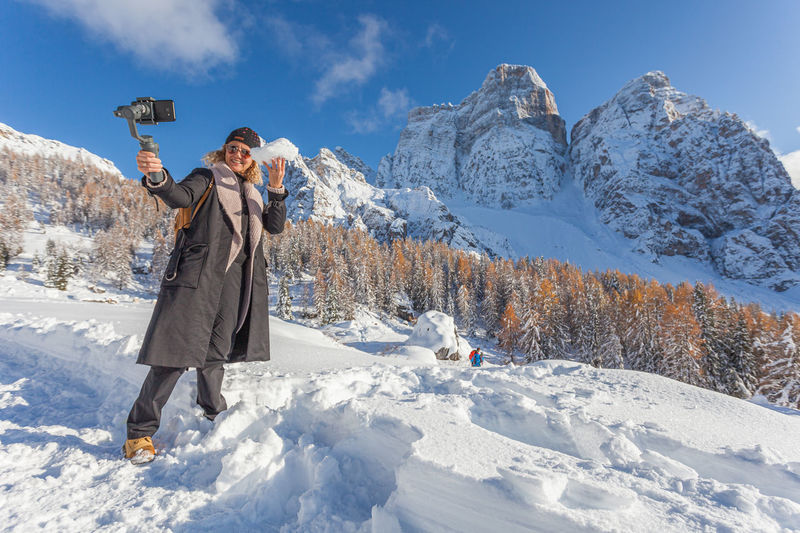 Blonde girl with a snowball in her hand take photo with phone of awesome snowy landscape, dolomites