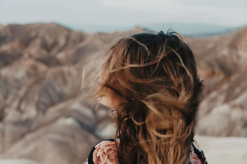 woman in front of a desert landscape As her blond hair blows wild in the wind Female Beauty In Nature Wild Free Windy Brown Woman EyeEm Selects Headshot Hair Hairstyle Women One Person Adult Real People Lifestyles Long Hair Portrait Brown Hair Focus On Foreground Sky Wind Nature Land Environment