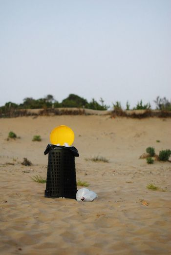 Rear view of hat on beach against clear sky