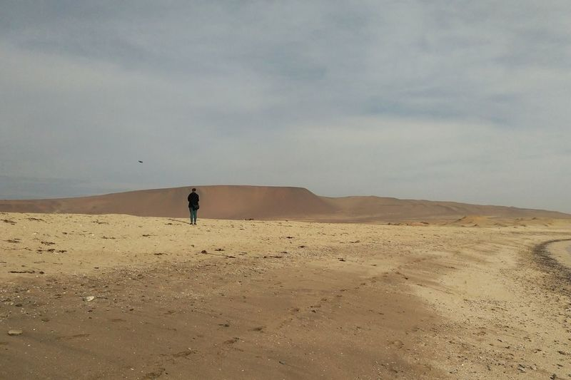Scenic view of desert against sky with a person