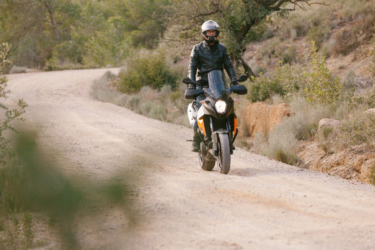 Man riding motorcycle on dirt road
