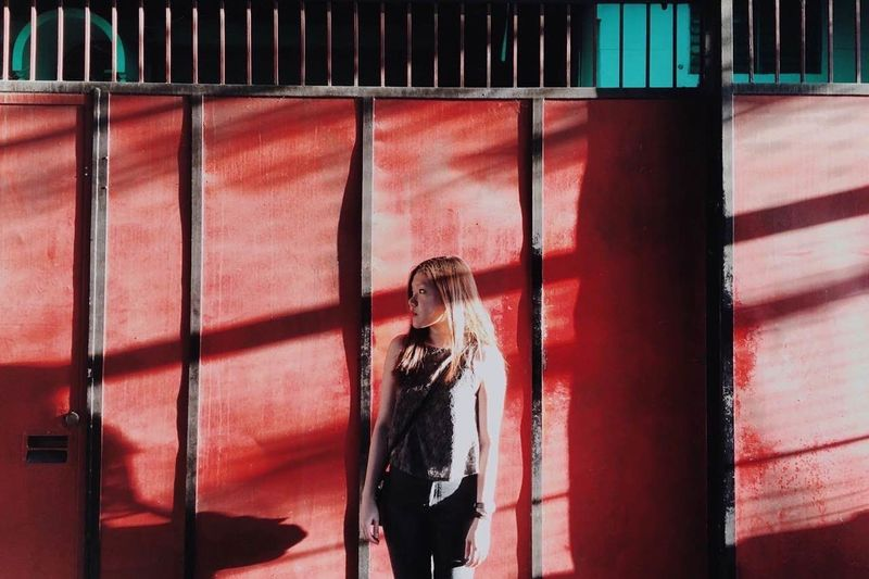 Young woman standing against red wall