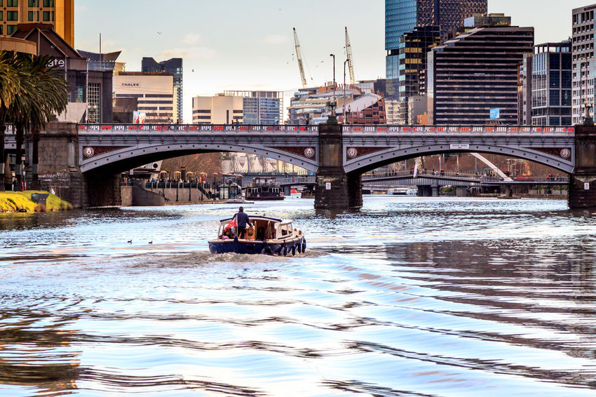 Cruising down the Yarra River towards the CBD Arch Architecture Bridge - Man Made Structure Building Exterior Built Structure City Connection Day Mode Of Transport Nature Nautical Vessel Outdoors Real People River Sky Transportation Water Waterfront
