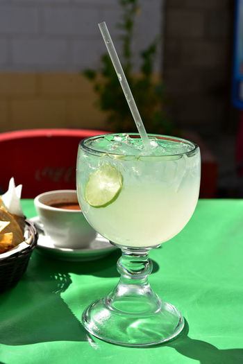 Large glass of lemonade with lime slice in glass served in restaurant in baja mexico