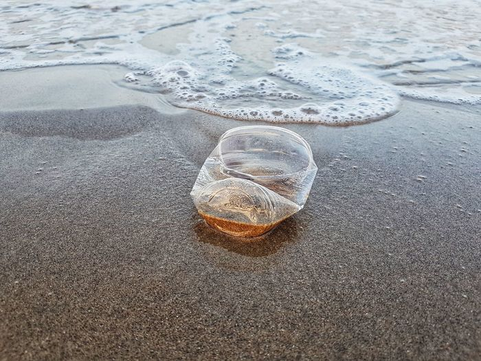 Cup Plastic Environment Pollution Nature Human RISK Danger Concept Save Stop Danger Life Sea Catastrophe Destroy Desaster Natural Water Sea Beach Sand Shore Tire Track Close-up Wave Crashing Coast Seashore Tide