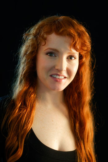 Black Background Redhead Adult Adults Only Beautiful Woman Black Background Close-up Curly Curly Hair Day Fair Skin Ginger Headshot Long Hair Looking At Camera One Person One Woman Only One Young Woman Only People Portrait Real People Red Hair Redhead Smiling Studio Shot Young Adult Young Women