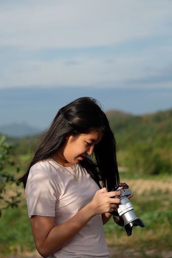 Young woman looking at dslr while standing on grassy field against sky