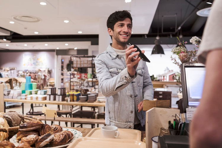 Smiling young man standing at store