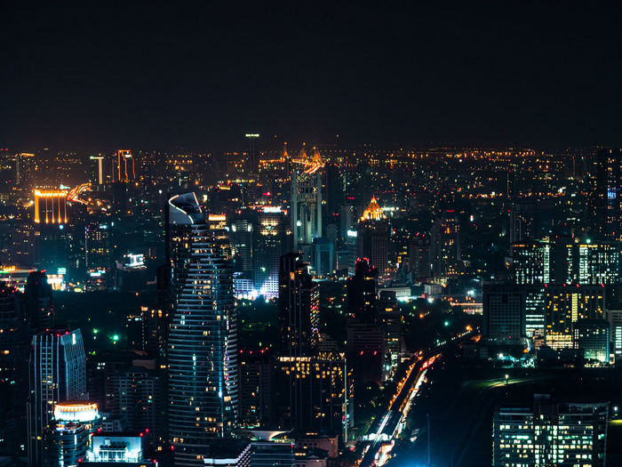 High angle view of illuminated city buildings against sky at night