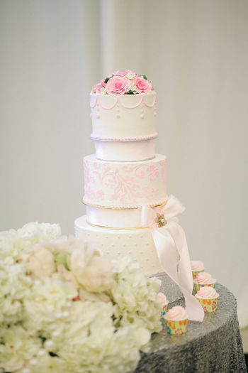 Cake on table against white wall