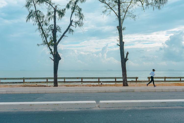 Man walking on road by sea against sky
