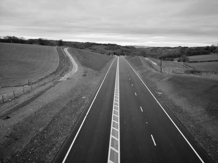 Looking like the 60's.. The new open Newtown Bypass... Think it's getting by-passed... If I leave here tomorrow Would you still remember me? For I must be traveling on now 'Cause there's too many places I've got to see. But if I stayed here with you, girl, Things just couldn't be the same. 'Cause I'm as free as a bird now, And this bird you cannot change. And this bird you cannot change. And this bird you cannot change. Lord knows I can't change. Bye, bye, baby, it's been a sweet love, yeah, Though this feeling I can't change. But please don't take it so badly, 'Cause Lord knows I'm to blame. But if I stayed here with you, girl, Things just couldn't be the same. 'Cause I'm as free as a bird now, And this bird you'll never change. And the bird you cannot change. And this bird you cannot change. Lord knows, I can't change. Lord, help me, I can't change. Lord, I can't change. Won't you fly high, free bird, yeah? Which Direction? Should I Go Or Should I Stay ByPass BypassRoad Newtown Powys From Above  Level Lines&Design Black And White For The Love Of Black And White Lines Light And Shadow Shades Shades Of Grey Light The Way Forward To Country Roads The Way Forwards Is To The Past Road Straight Diminishing Perspective Sky Landscape Empty Road Highway Road Marking Asphalt vanishing point The Way Forward Two Lane Highway