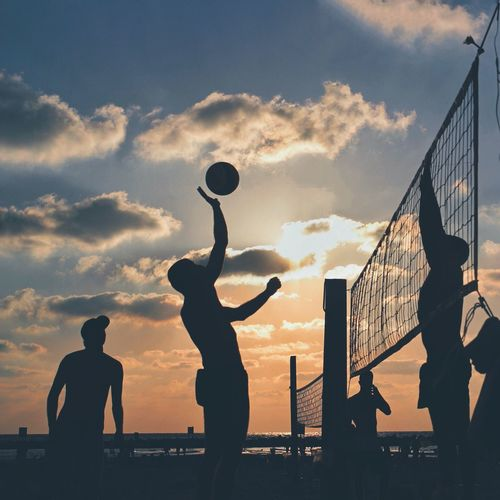 Silhouette men playing volleyball at beach against sky