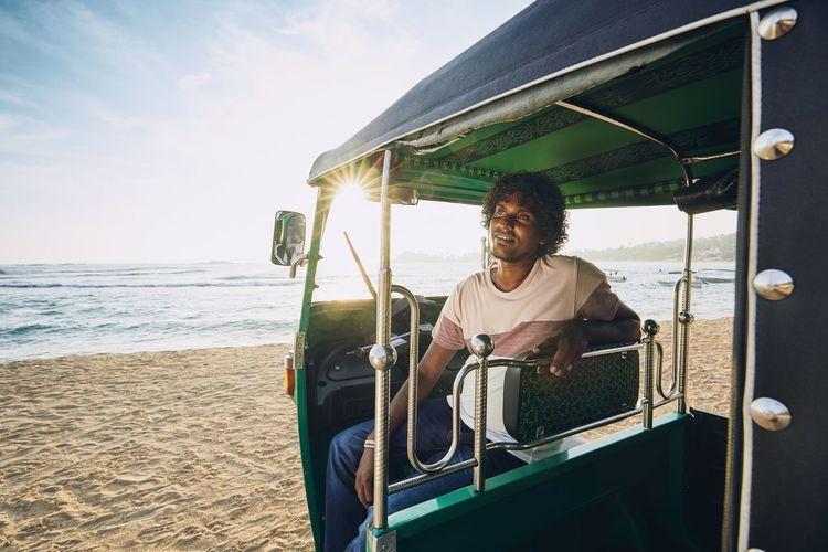 Smiling man sitting in rickshaw at beach against sky