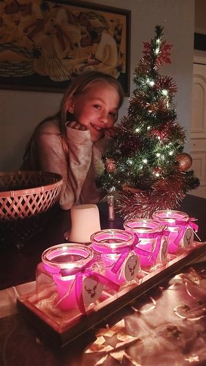Girl in illuminated christmas tree at home