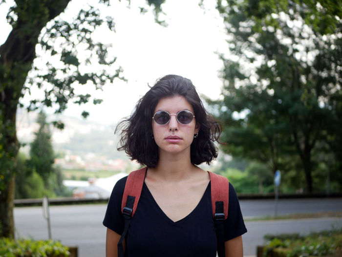 Glasses Portrait Of A Woman PortraitPhotography Backpack Beautiful Woman Fashion Focus On Foreground Front View Glasses Hair Hairstyle Headshot Leisure Activity Lifestyles Looking At Camera One Person Outdoors Plant Portrait Real People Standing Sunglasses Tree Young Adult Young Women