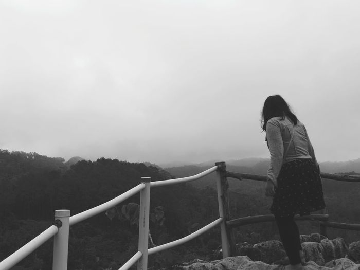 Side view of woman standing on railing against sky