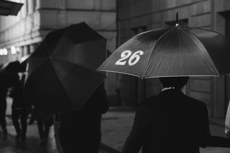 Rear View Of Man Holding Umbrella With Number In City During Monsoon