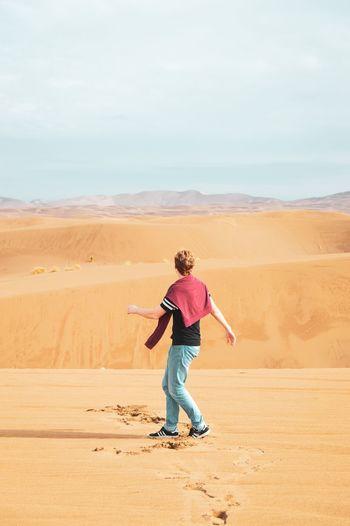 Full length of woman on sand dune