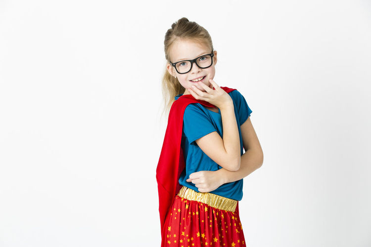 Cute Playful Girl Wearing Red Cape Standing Against White Background