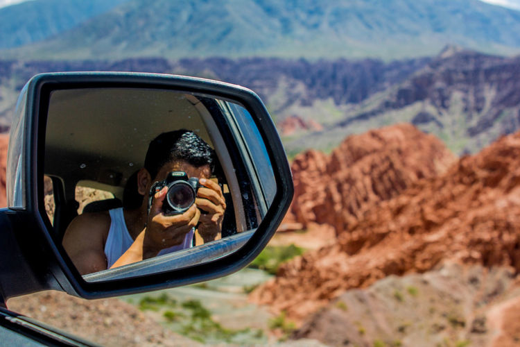 Man photographing while reflecting on side-view mirror of car