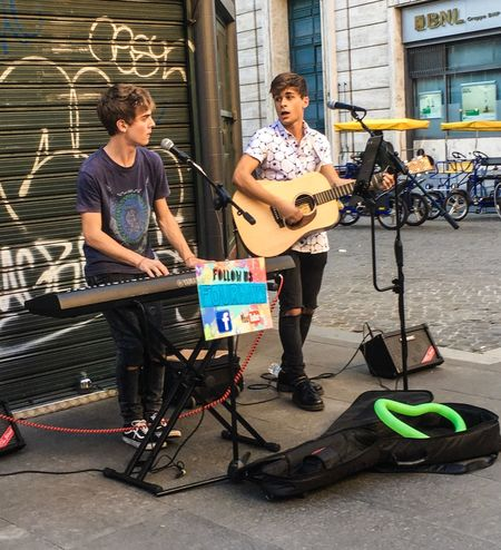 Full Length Casual Clothing Leisure Activity Person Lifestyles Young Adult Young Men City Front View Looking Away Friendship Confidence  Architecture Music Music Brings Us Together Musician Band Street Performers Guitar Keyboard