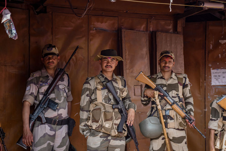 Portrait of army soldiers with guns standing against built structure
