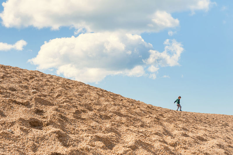 Low angle view of boy standing on sand dune against sky