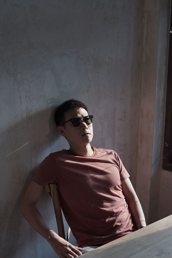 Young man wearing sunglasses sitting against wall