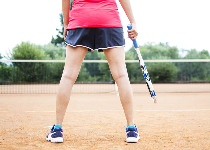Low section of woman playing tennis on court