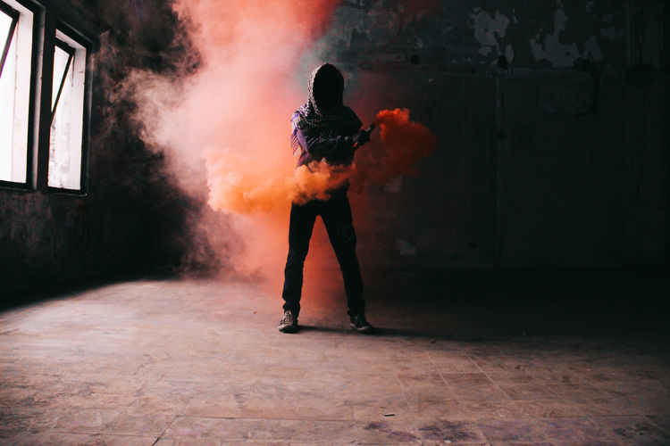 Man holding distress flare while standing in abandoned room