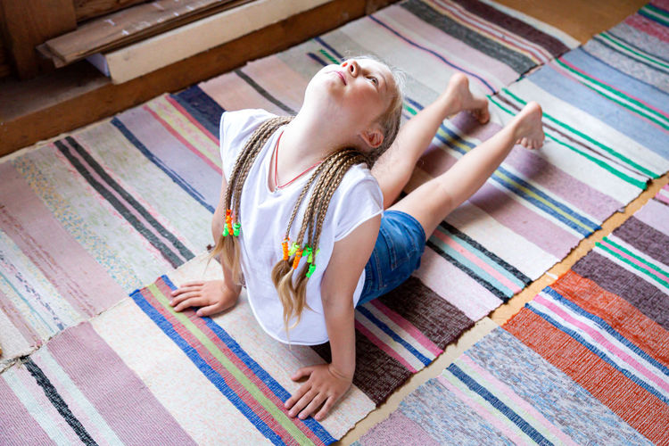 Caucasian girl with braids in a white t-shirt is doing yoga, stretching at home on a striped rag