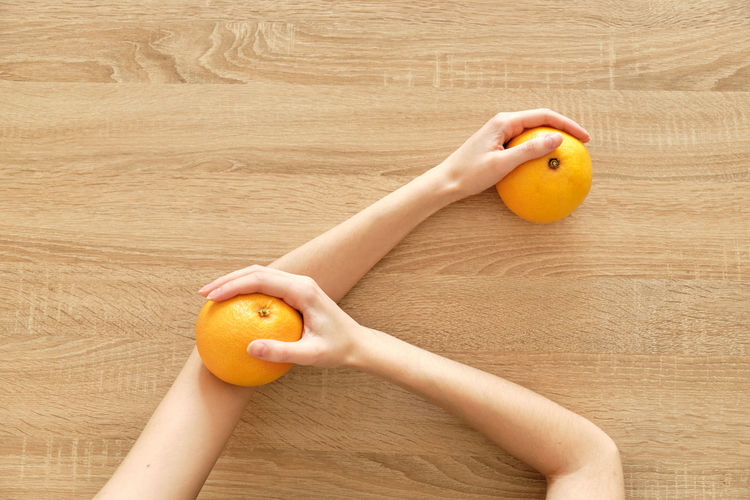 Cropped image of hand holding orange fruit on floor